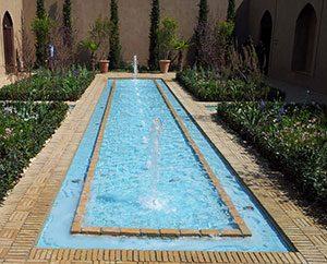 Ein Wasserbecken mit Springbrunnen als zentrales Element des Gartens.